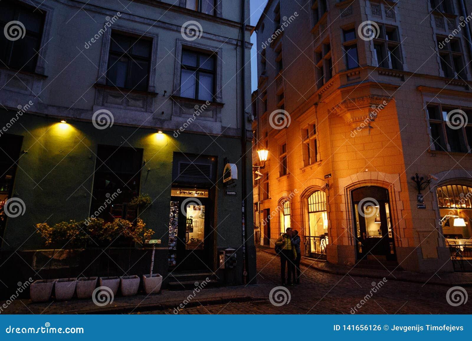 Riga vieja en la noche, Letonia, Europa - gente que camina en las calles históricas de la capital europea