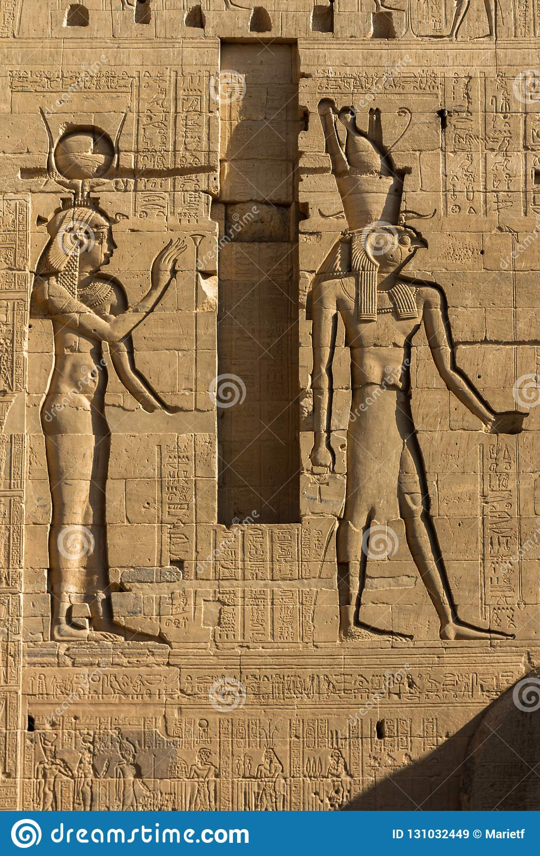 Relief carvings of hathor and osiris on the first pylon of the