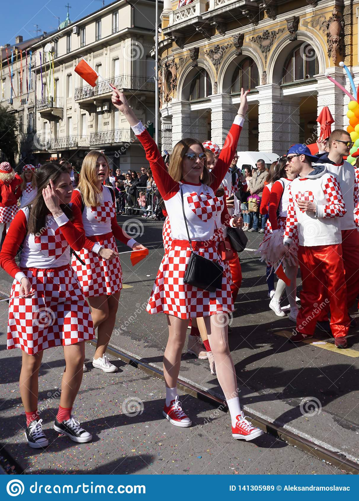 Girls with national Croatian symbol costume, singing and celebrate in the street of town Rijeka at the carnival procession