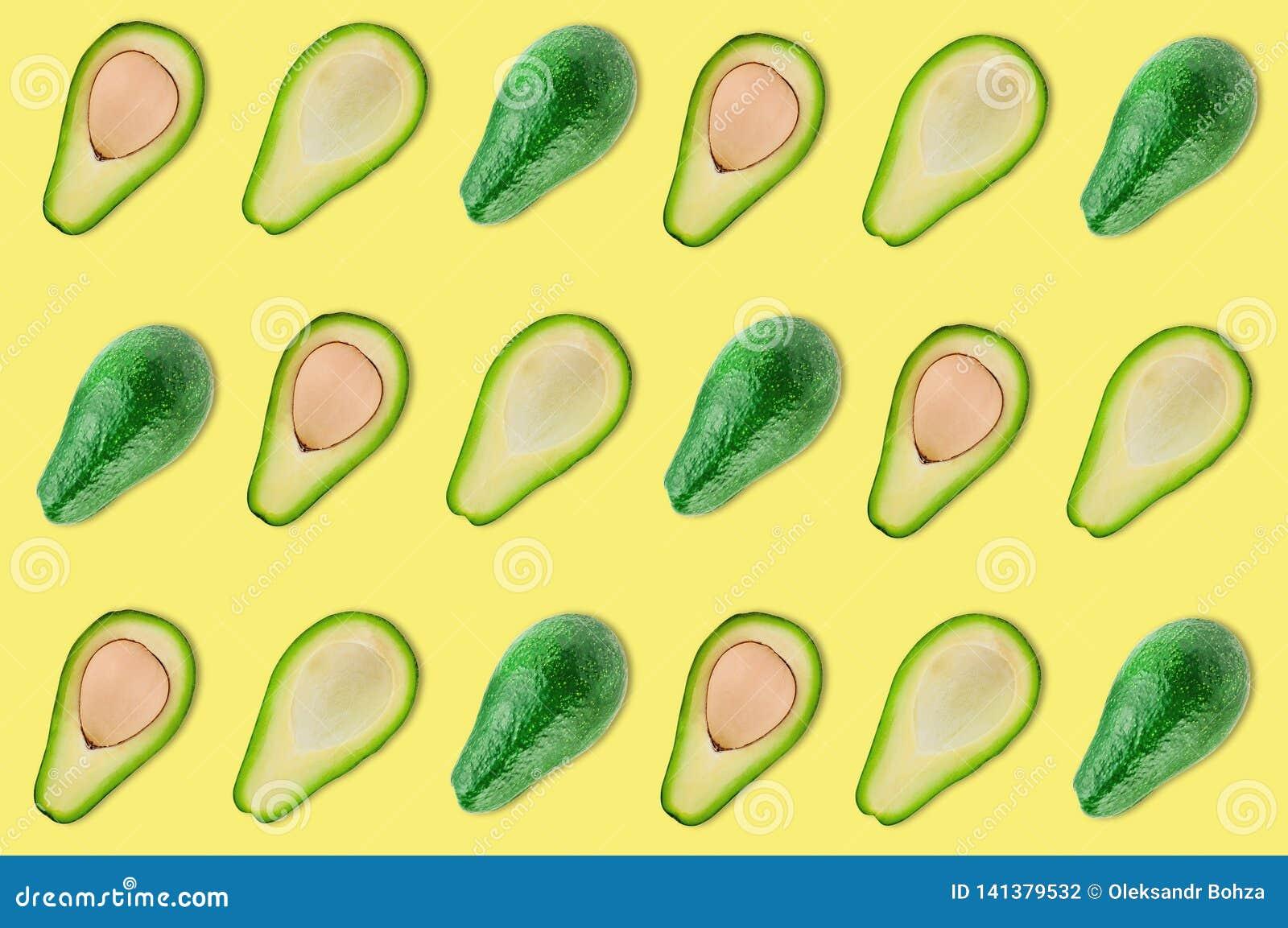 Rijen van geheel en de helften van organische avocado met en zonder pitten in centrum van gele lijst in keuken of markt