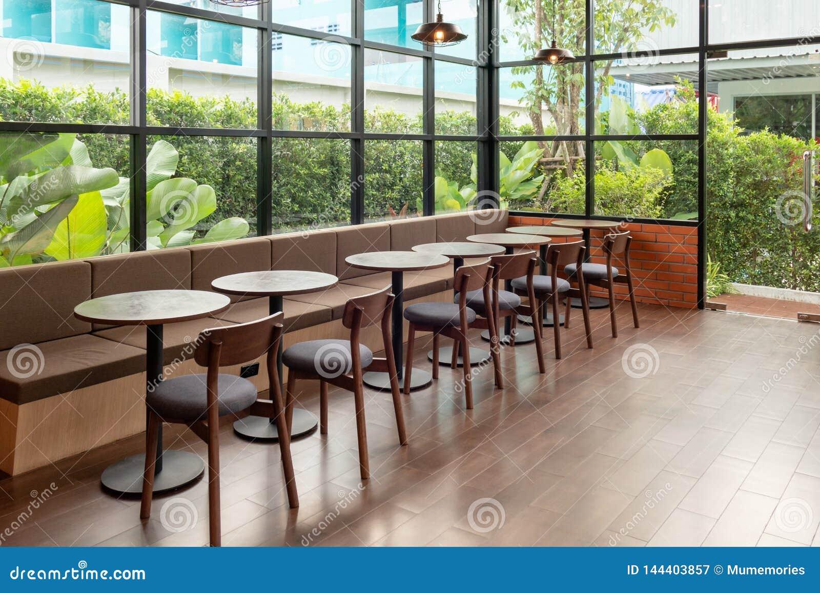 Rijen van houten lijst en stoel binnen van glasruimte met tuin