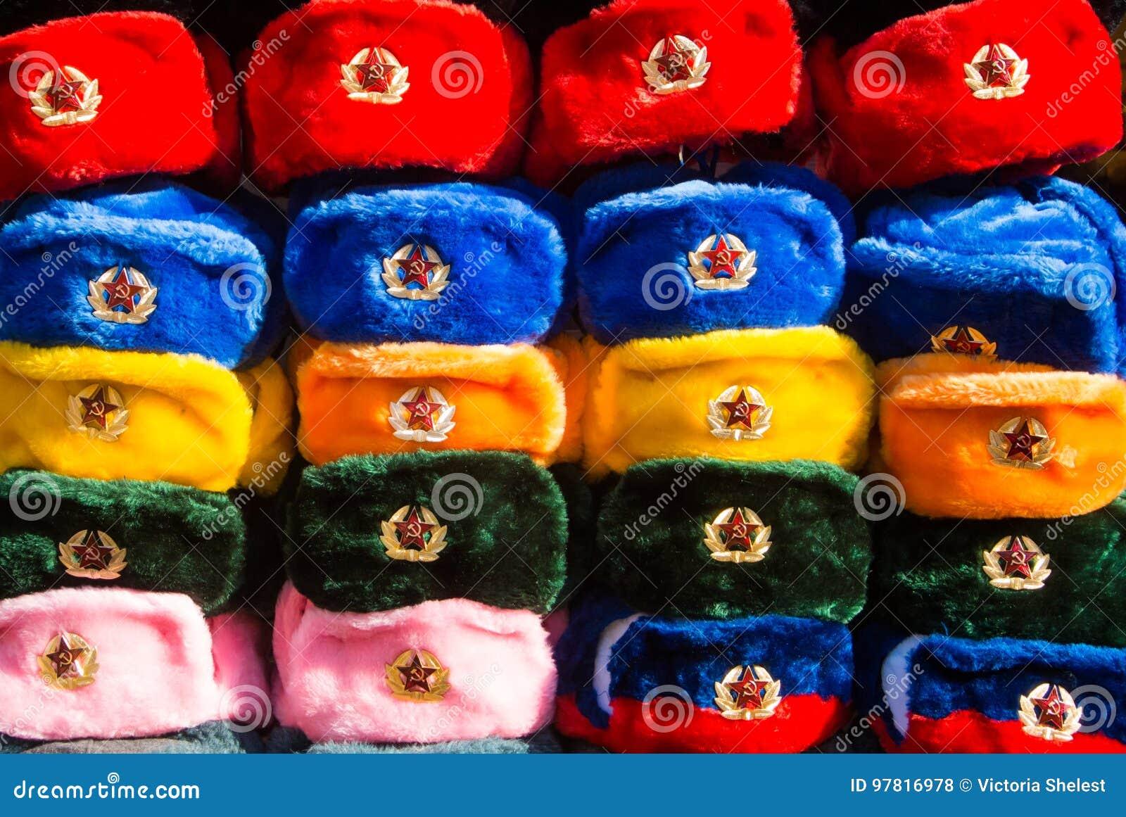 Rijen van Russische de winterhoeden van verschillende kleuren met legeremblemen bij de straatmarkt bij Oude Arbat-straat