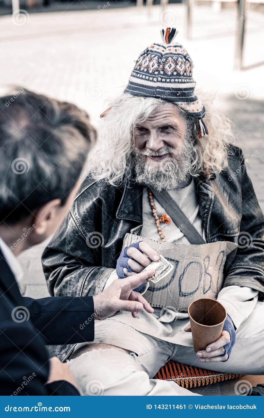 Rijke man die aan handeling van liefdadigheid deelnemen terwijl het overhandigen van geld aan daklozen