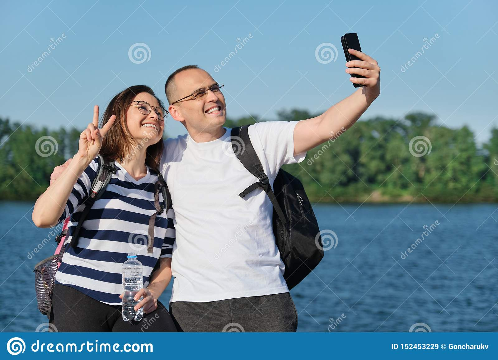 Rijp gelukkig paar die selfie foto op telefoon nemen, mensen die dichtbij rivier in het park van de de zomeravond ontspannen