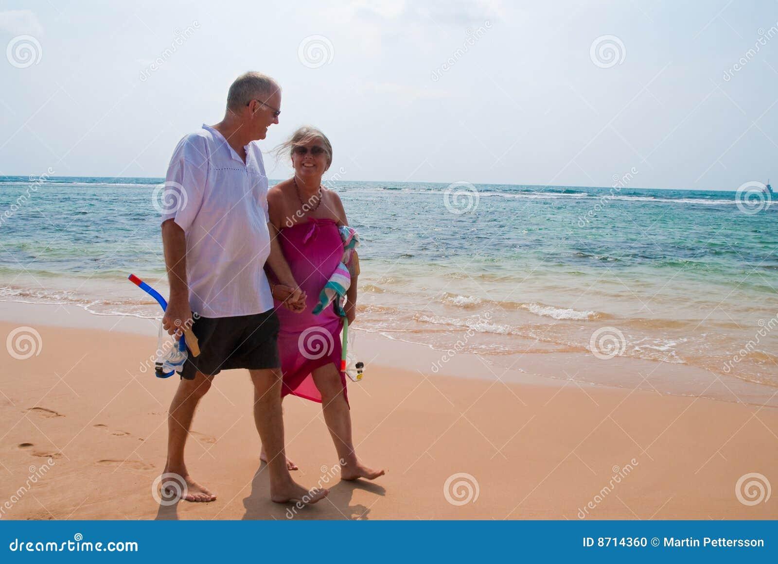 Rijp paar dat op strand loopt