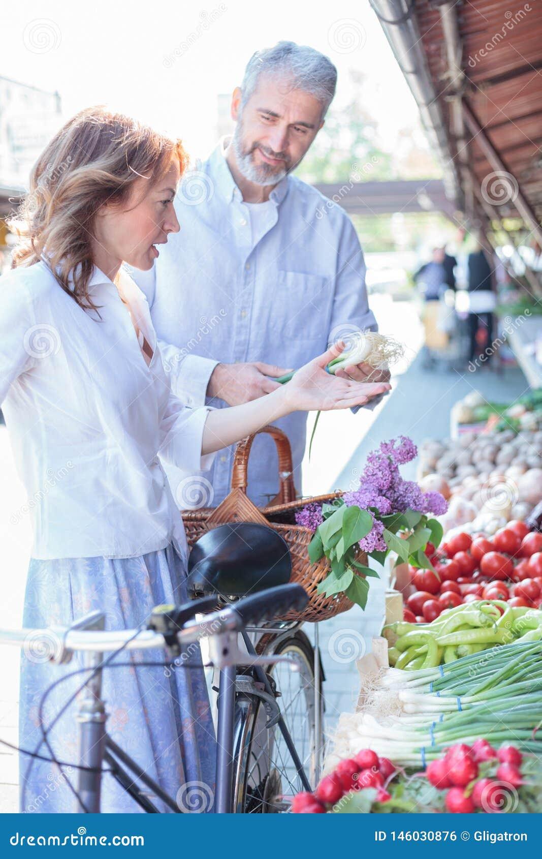 Rijp paar die verse organische groenten in een openluchtmarkt kopen