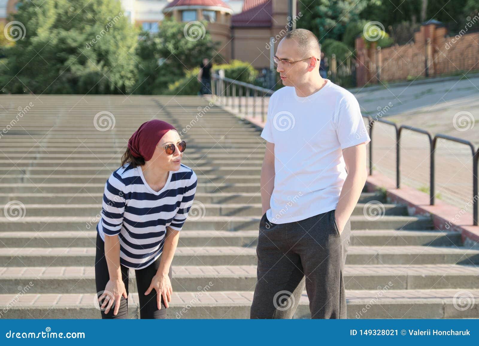 Rijp paar in stad dichtbij de treden, man en vrouw op middelbare leeftijd in sportkleding spreken die na het lopen rusten