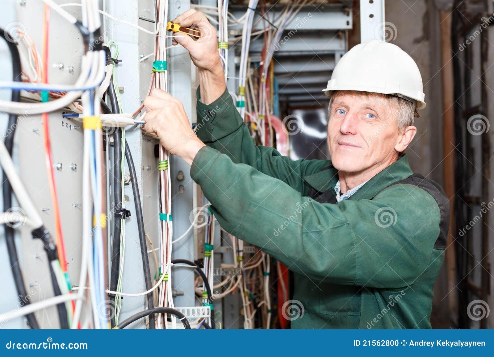 Rijpe elektricien die in bouwvakker met kabels werkt