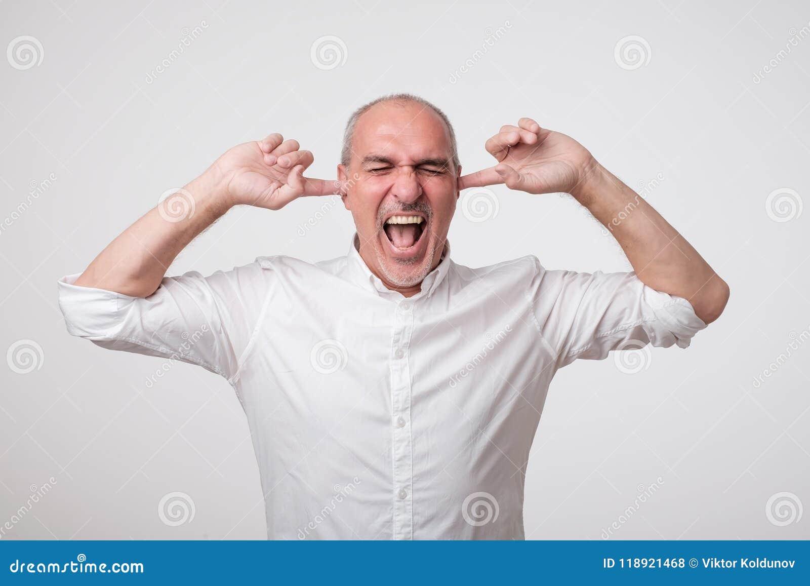 Rijpe Europese mens die zijn oren wegens hevig geluid en lawaai sluiten Ik wil niet luister aan u