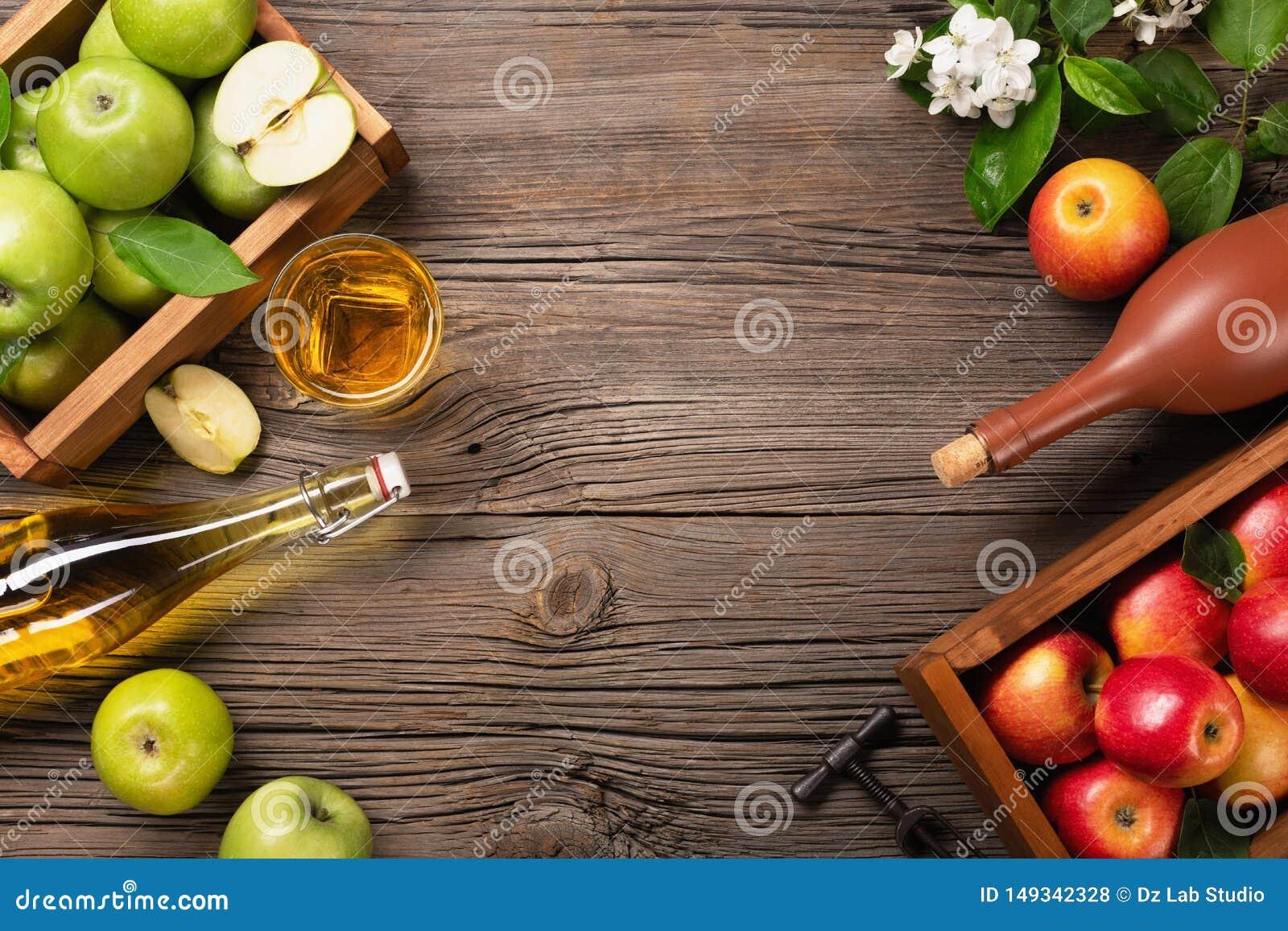Rijpe groene en rode appelen in houten vakje met tak van witte bloemen, glas en fles cider op een houten lijst