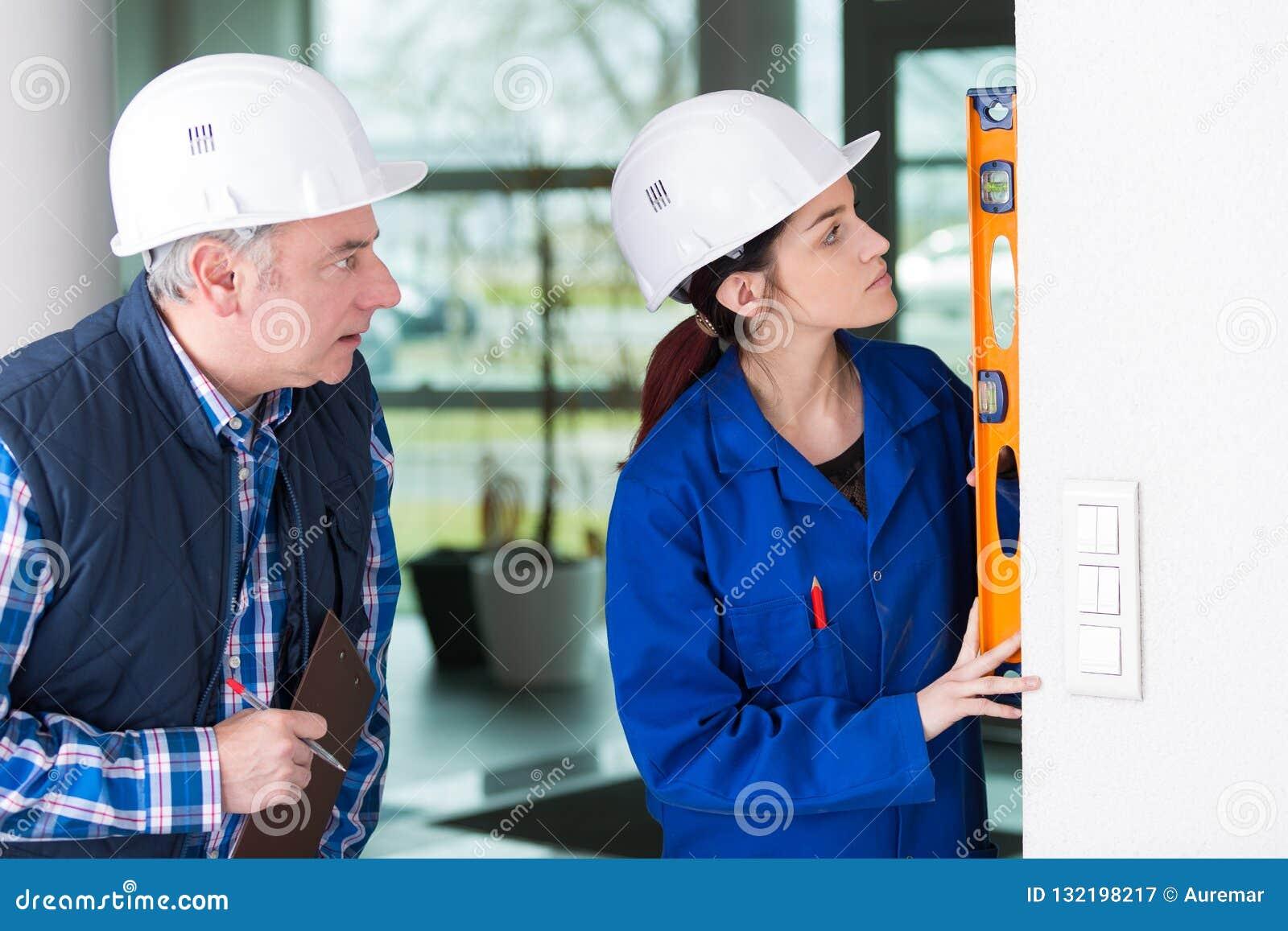 Rijpe hersteller die vrouw helpen om bouwersniveau te gebruiken
