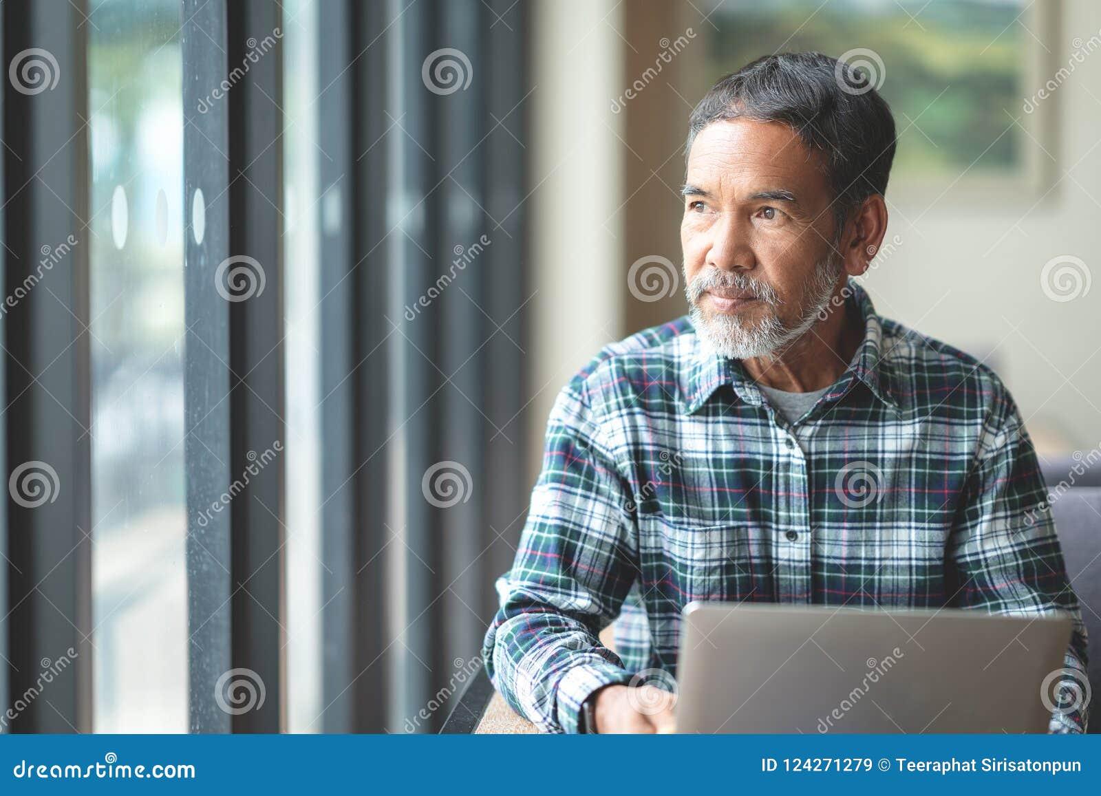 Rijpe mens die met witte modieuze korte baard buitenvenster kijken Toevallige levensstijl van teruggetrokken Spaanse mensen