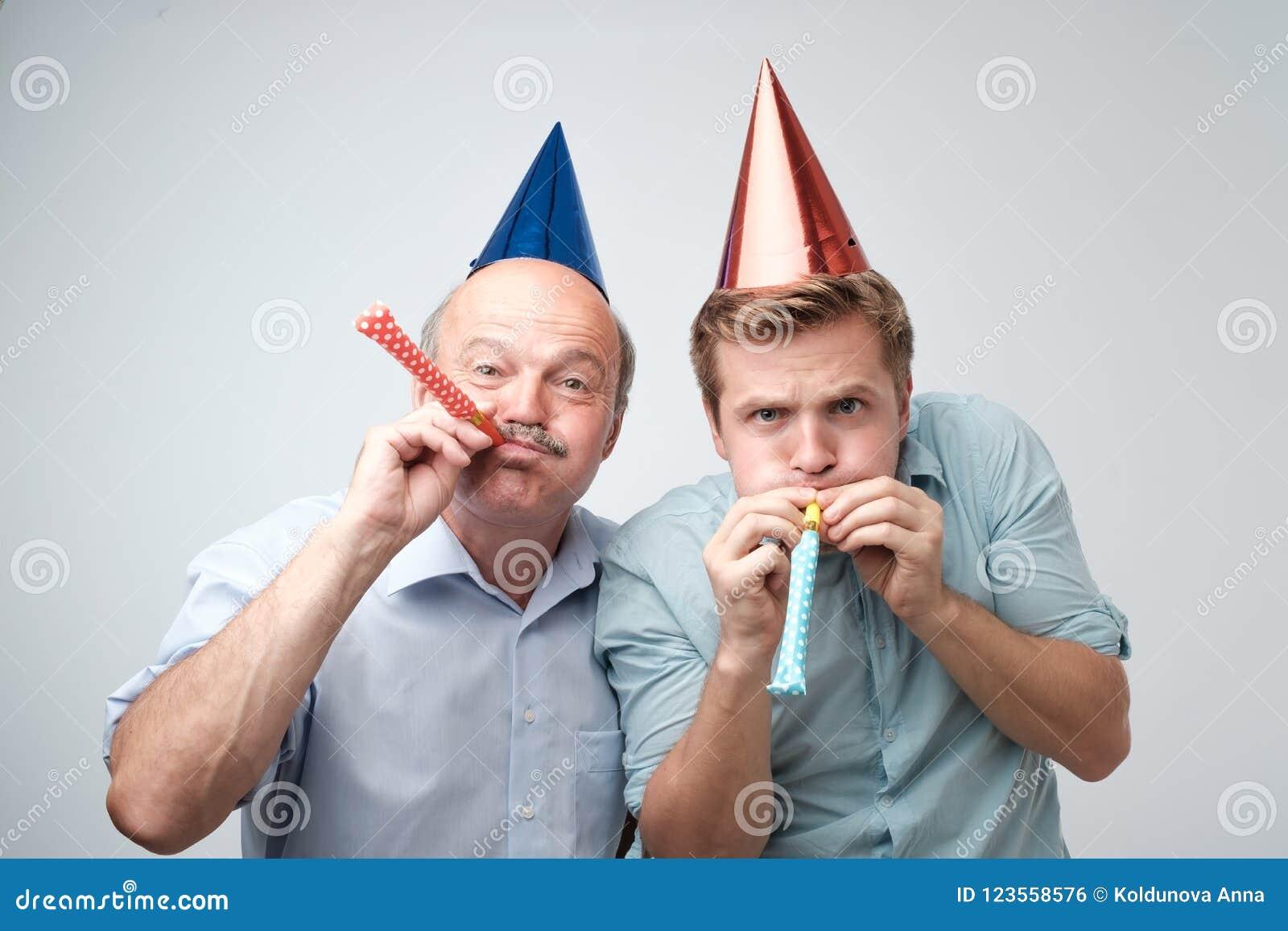 Rijpe mens en zijn jonge zoon die gelukkige verjaardag vieren die grappige kappen dragen