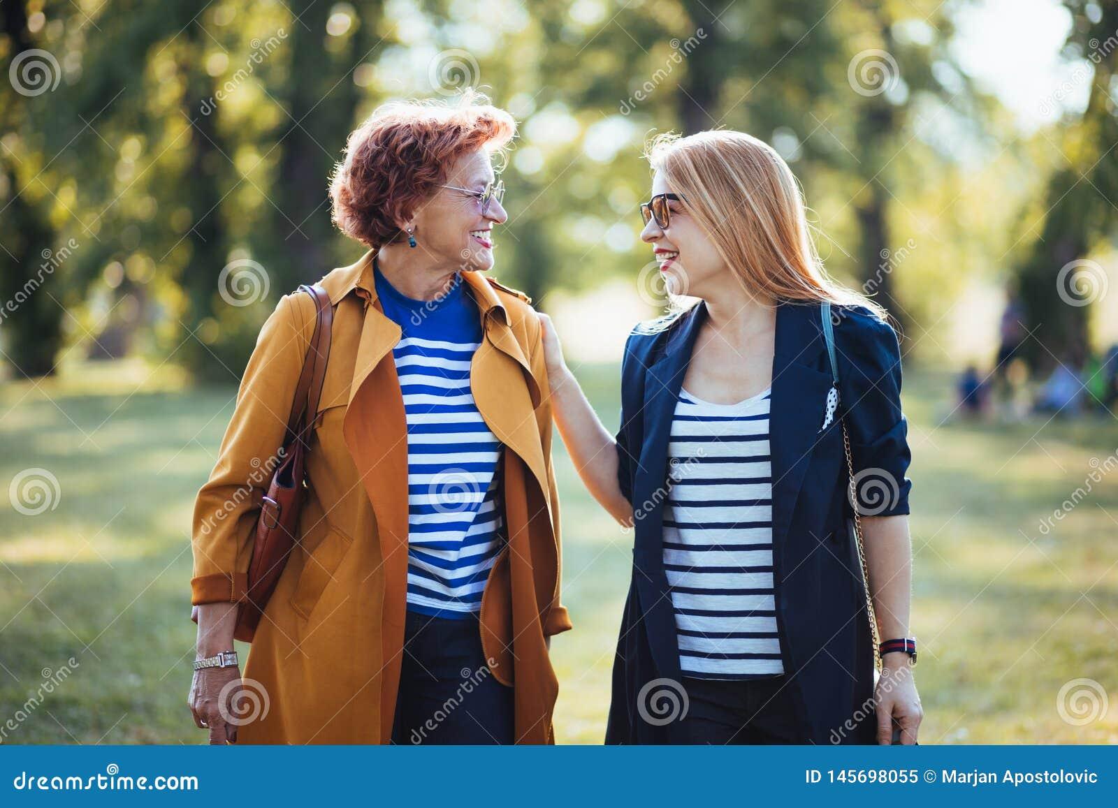 Rijpe moeder en volwassen dochter die van een dag in het park genieten