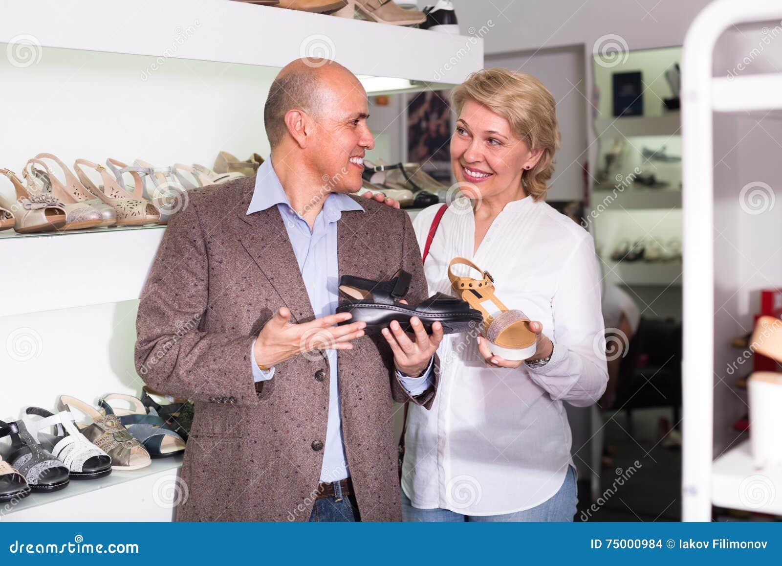Rijpe paar het plukken schoenen in boutique