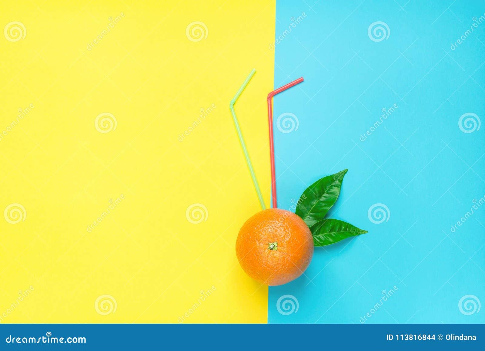 Rijpe Sappige Gehele Sinaasappel met Groen Bladeren het Drinken Stro op de Gele Blauwe Achtergrond van Duotone De verse Cocktails