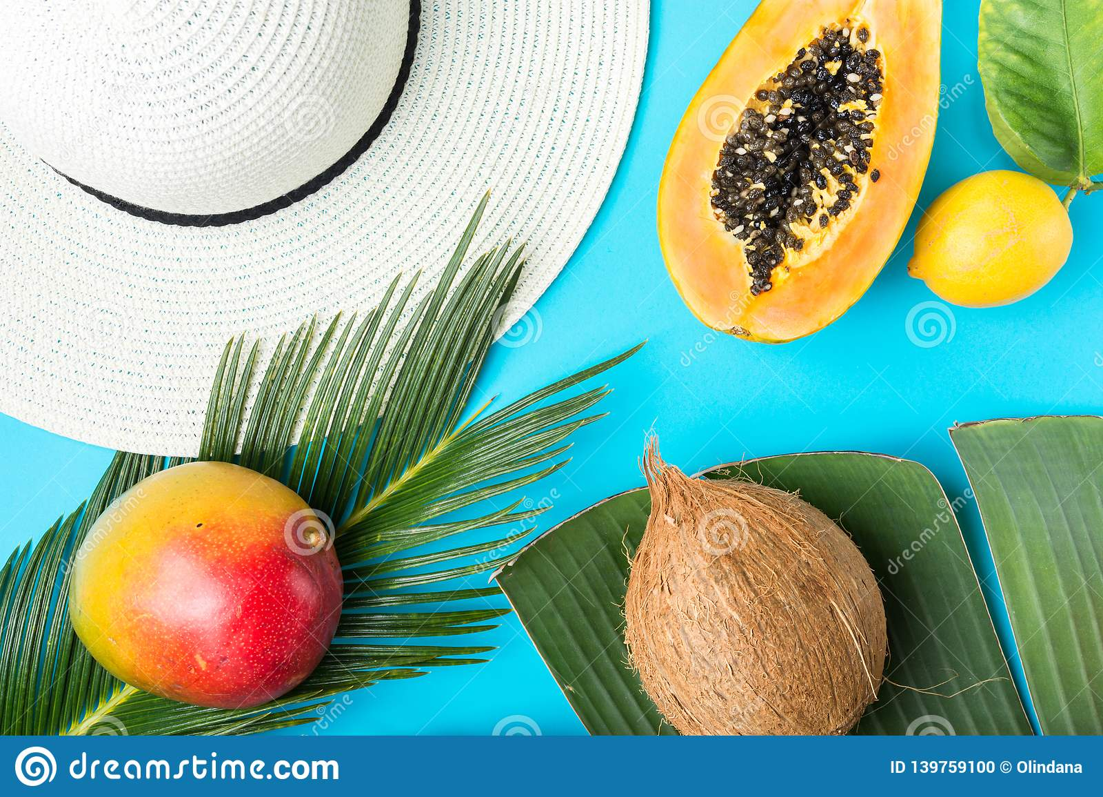 Rijpe sappige mango gehalveerde papajakokosnoot op groot palmblad De zonhoed van het strostrand op blauwe achtergrond De Manier v