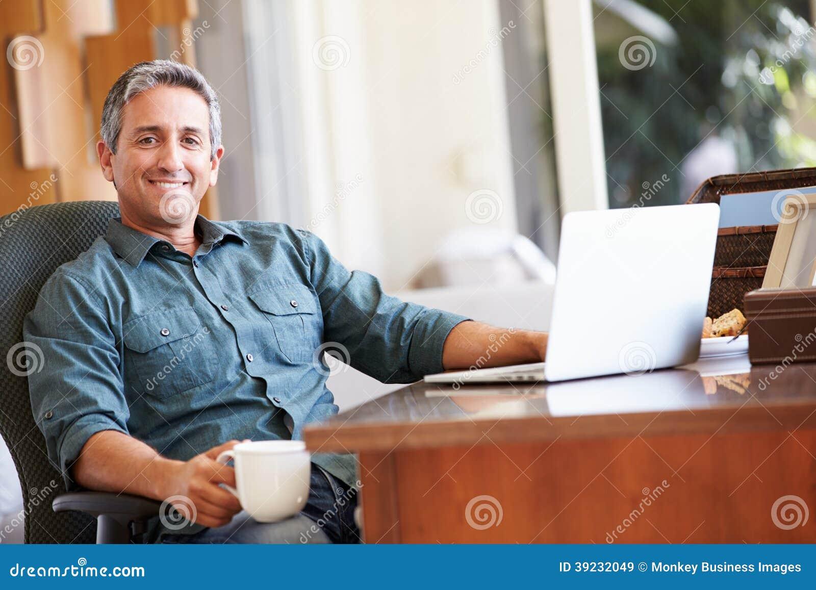 Rijpe Spaanse Mens die Laptop op Bureau thuis met behulp van