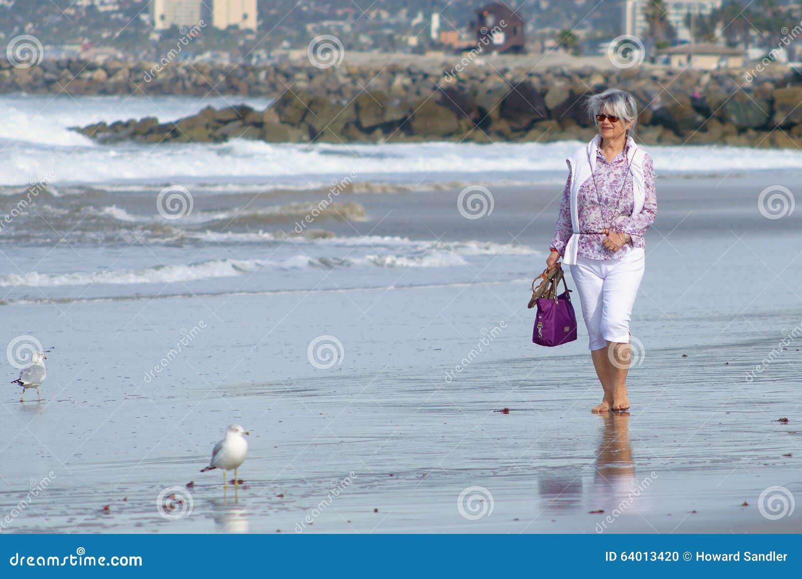 Rijpe vrouw die op strand lopen