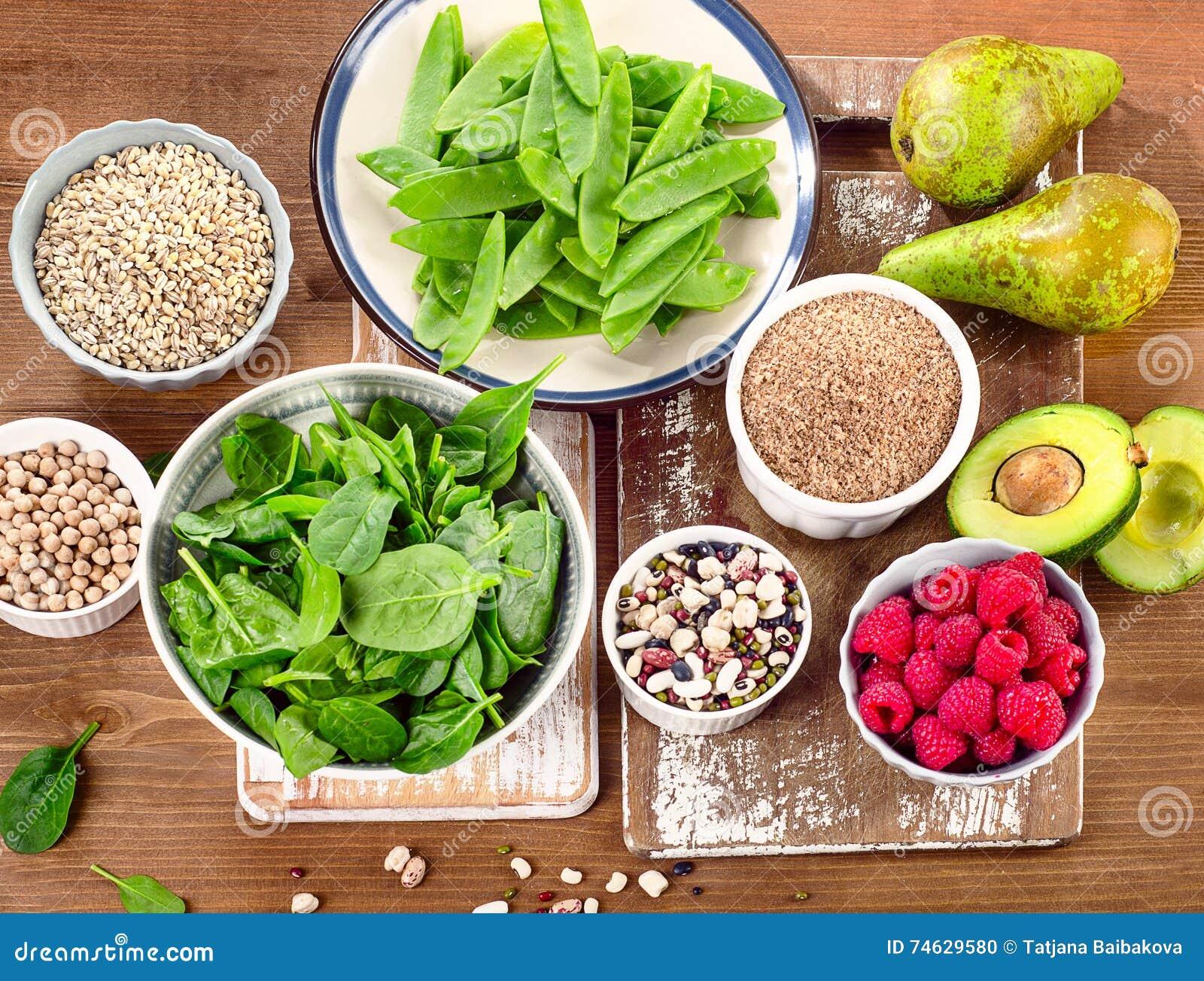 Rika foods för fiber och för carbs på ett träbräde Sunt banta eatinen
