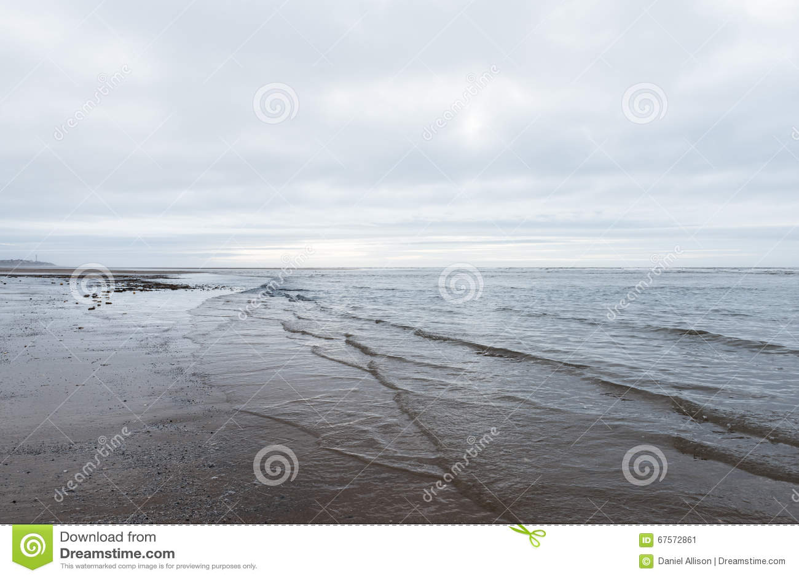 Rilassandosi ed addolcisca le onde calmanti che sfociano in una spiaggia un giorno nuvoloso triste