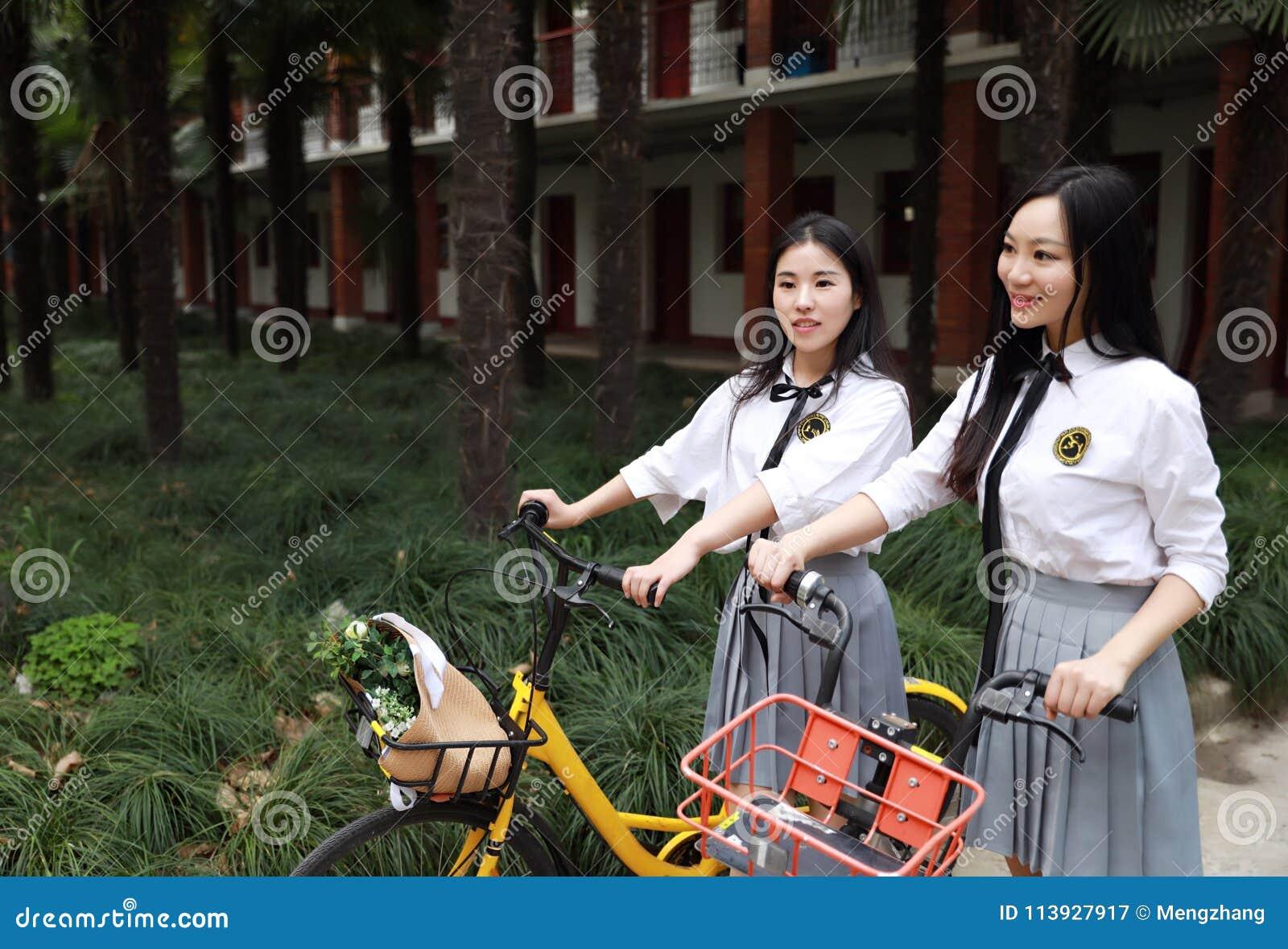 Rilassi lo studente che grazioso cinese asiatico di usura delle ragazze il vestito a scuola gode della bici di giro di tempo libe