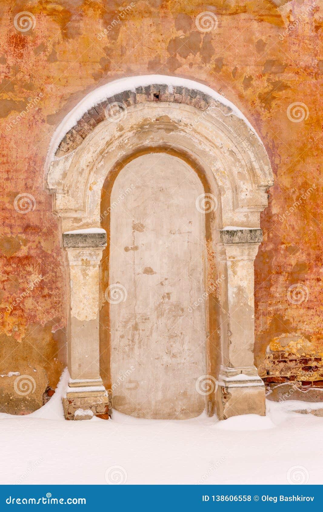 Rinchiuso bricked sulla porta con un portico e su due colonne dai lati sui precedenti di vecchia parete intonacata arancio dentro