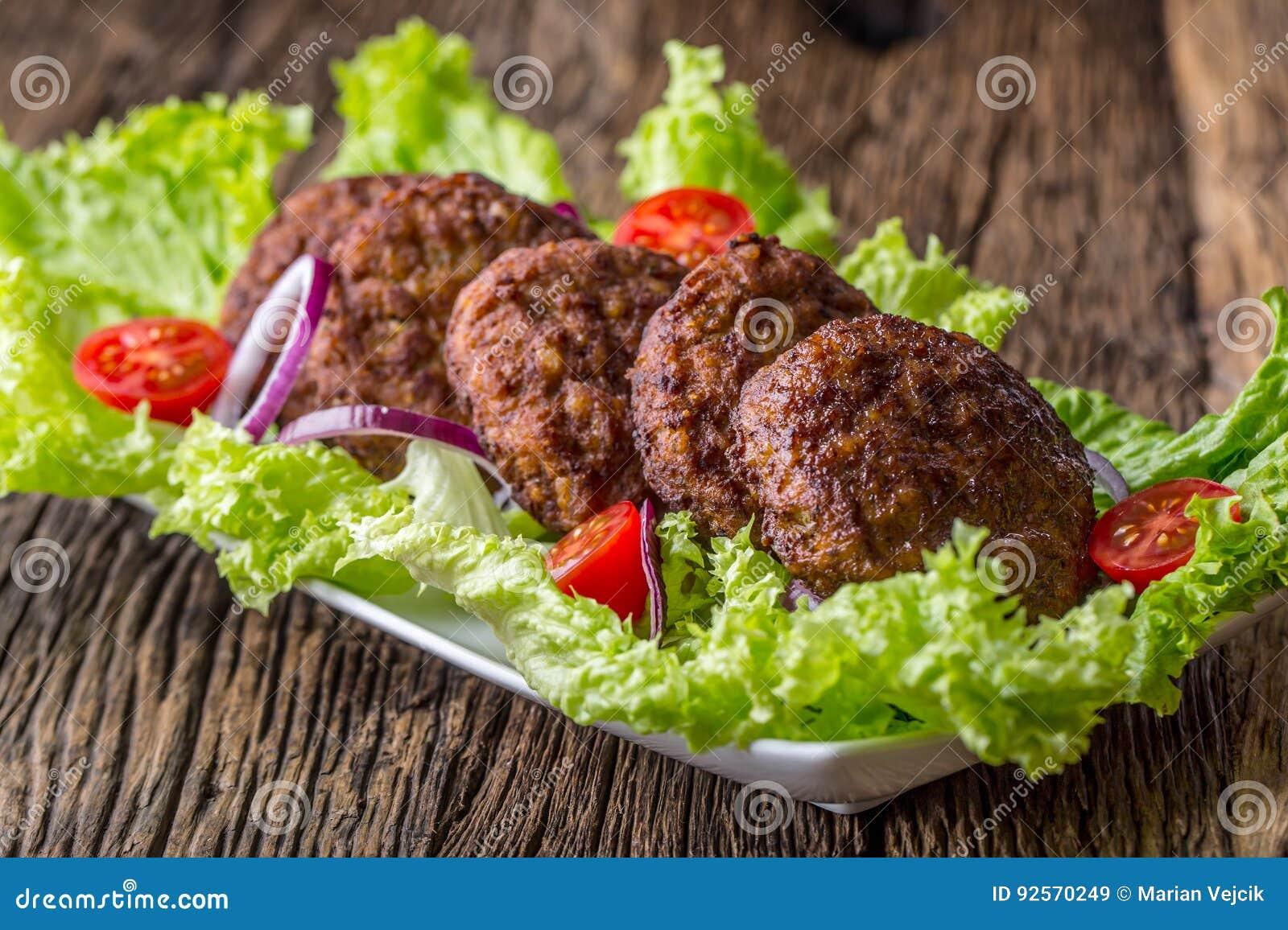 Rinforzi le cotolette delle polpette degli hamburger con la cipolla del pomodoro dell insalata della lattuga sul bordo di legno