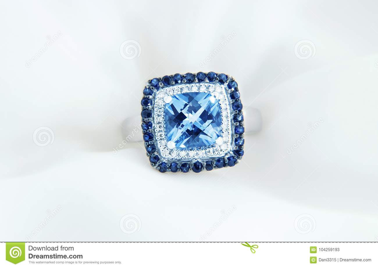 Ring with blue topaz and diamonds on soft white background