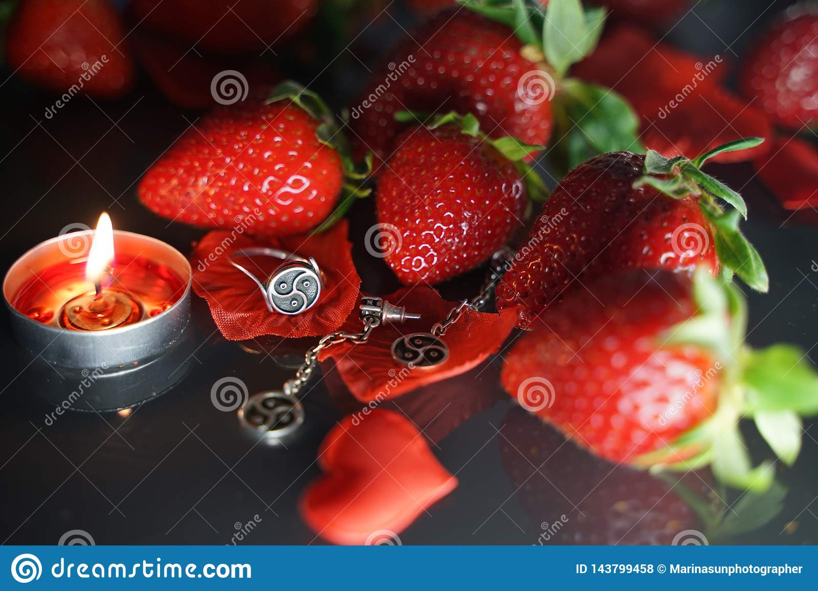 Ring and earrings with the symbol of bdsm lying among the strawberries on the black table top view