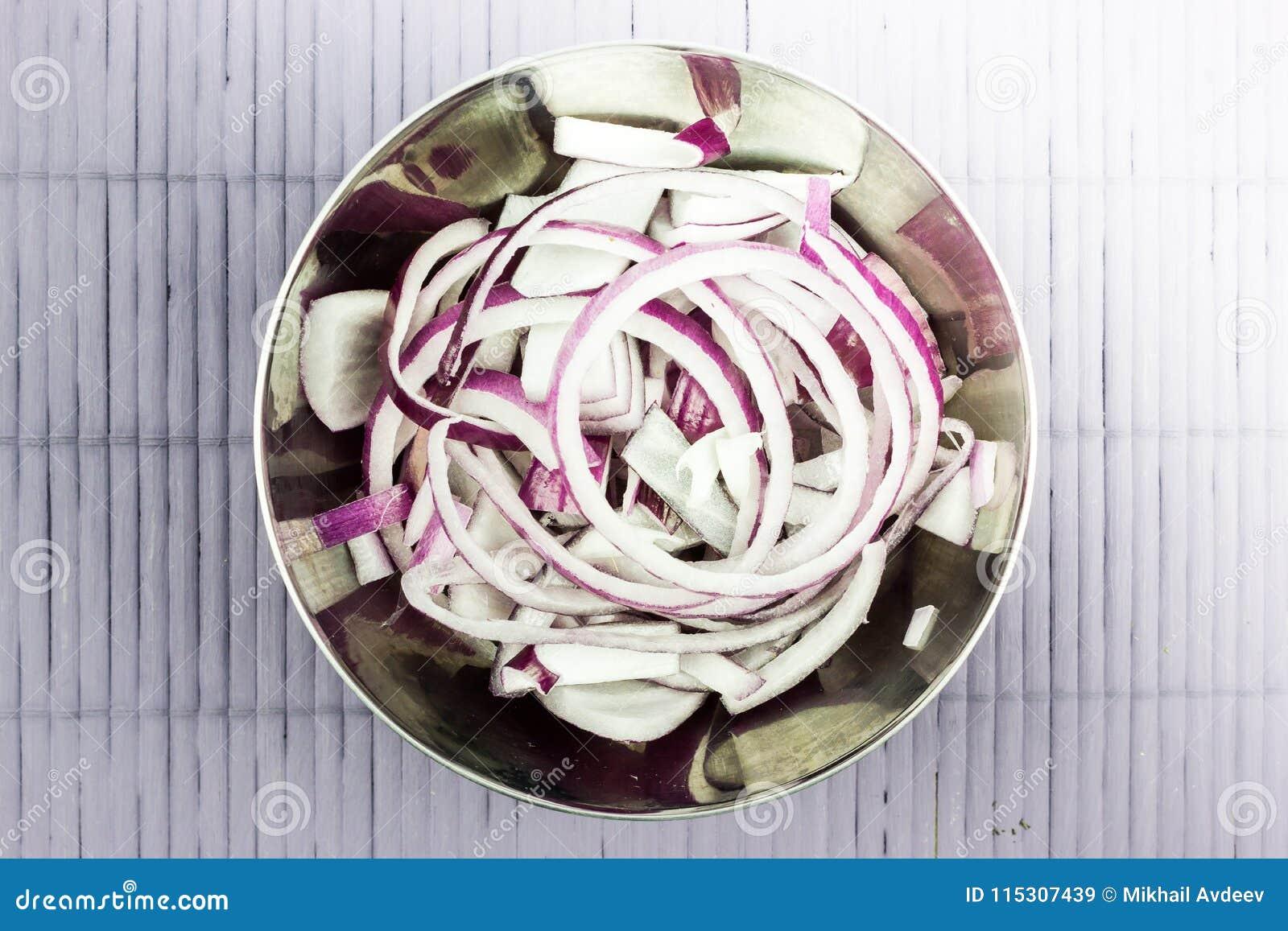 Ringe von purpurroten Zwiebeln in einem Metall rollen