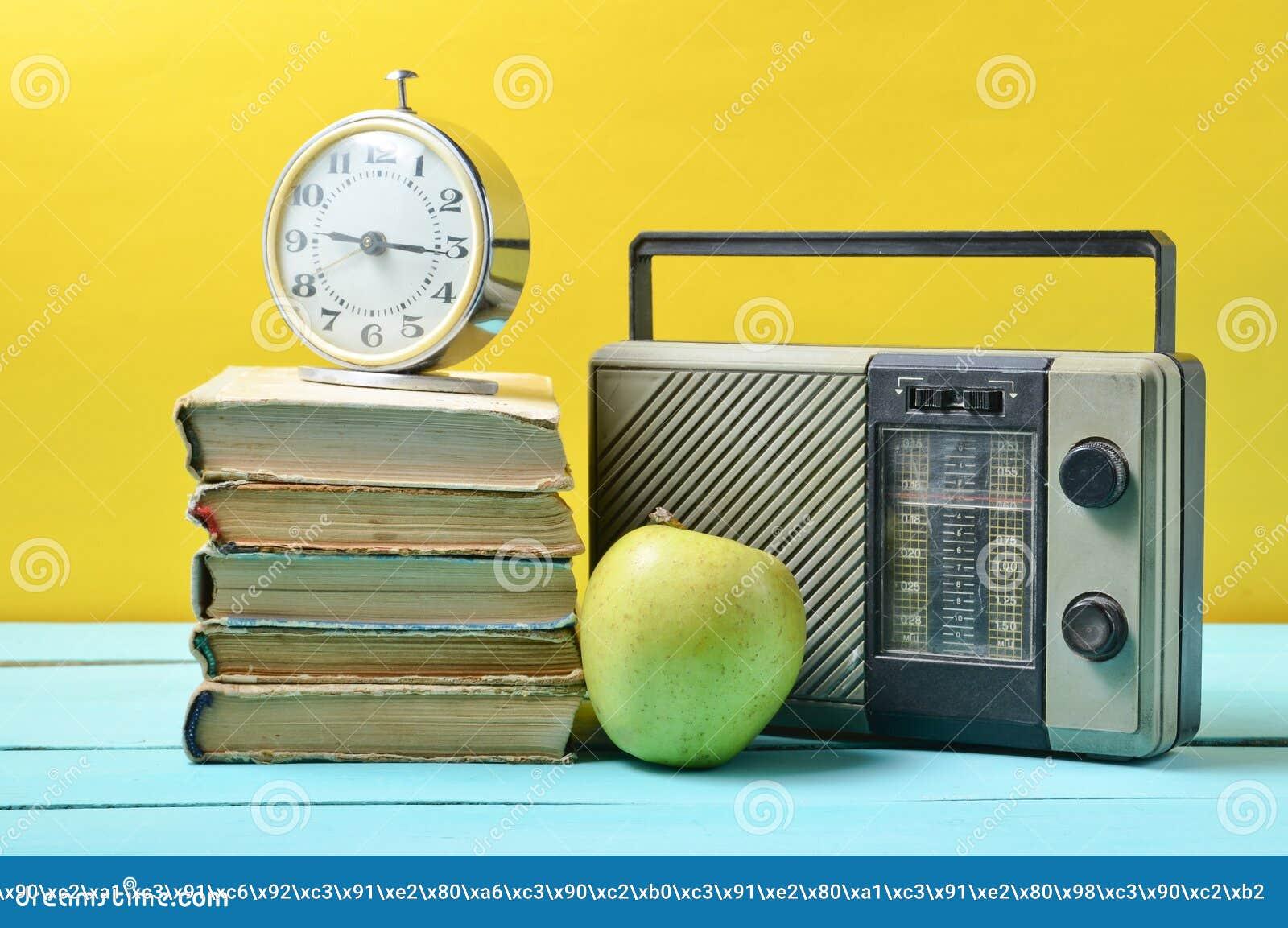 Ringklockan på bunten av gamla böcker, radiosänder mottagaren, äpple på en gul bakgrund retro livstid fortfarande