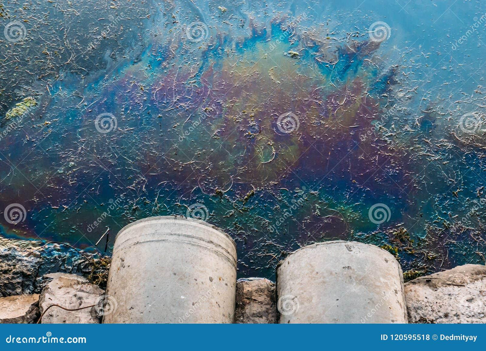 Rioolpijpen bij kust, vlek van olie of brandstof op waterspiegel, aardverontreiniging door giftige chemische producten, vuile ove