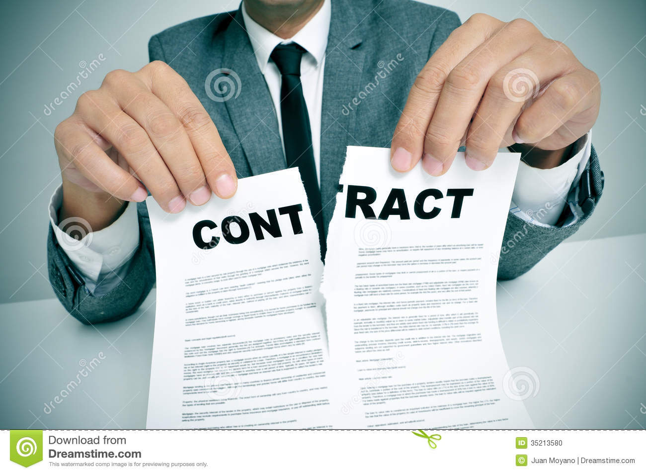 Man wearing a suit sitting in a table ripping up a contract.