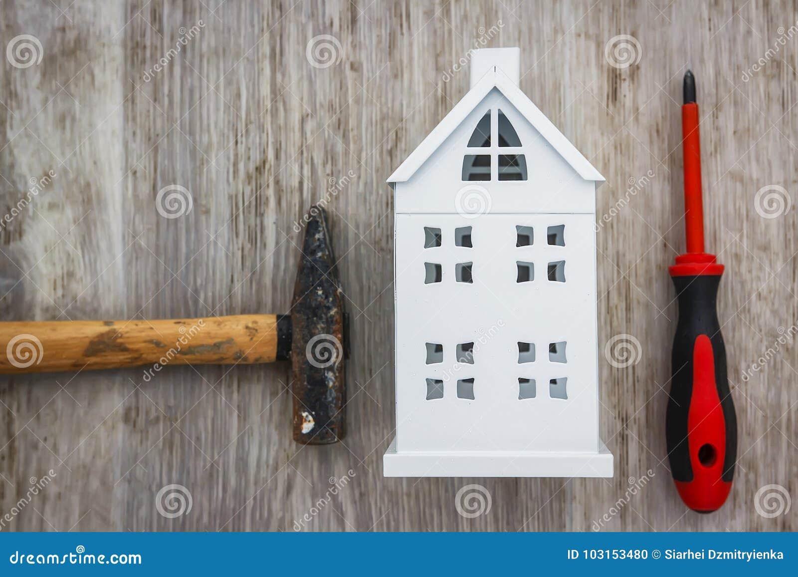 Riparazione del concetto della casa martello, cacciavite e casa miniatura su fondo di legno La costruzione foggia la casa della r