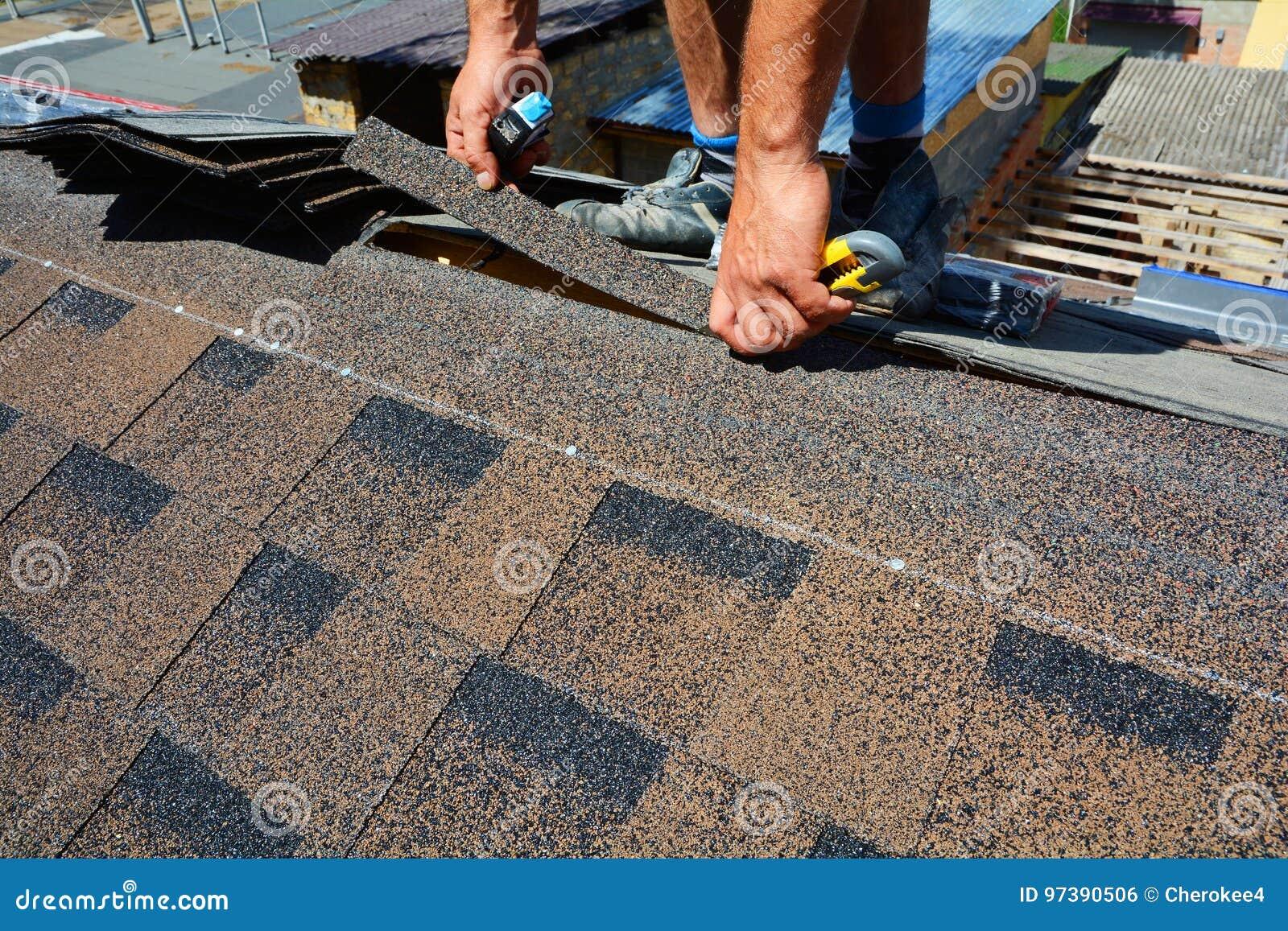 Riparazione di un tetto dalle assicelle Il feltro o il bitume del tetto di taglio del Roofer durante l impermeabilizzazione funzi