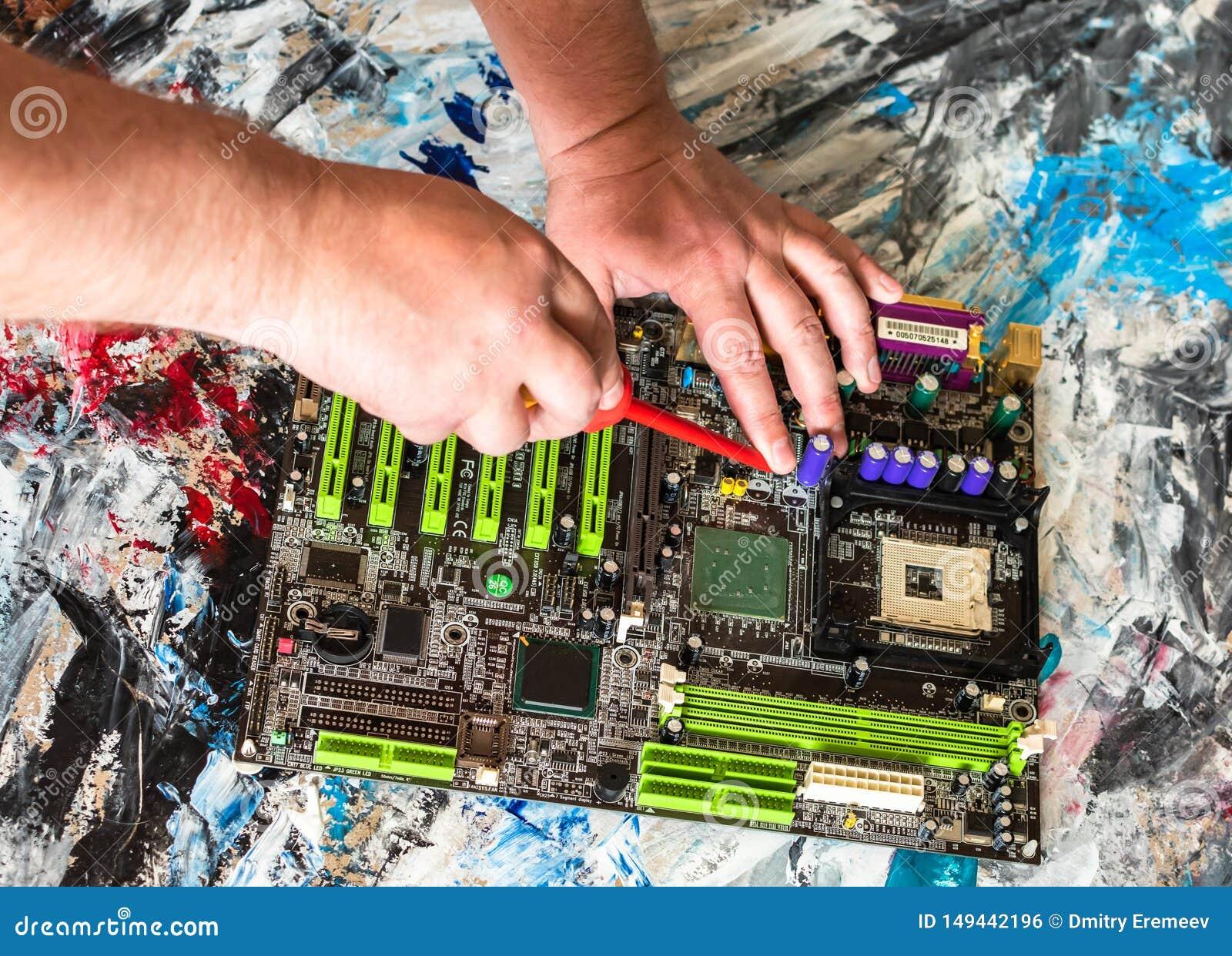 Riparazione di una scheda madre del PC con un cacciavite con una maniglia rossa