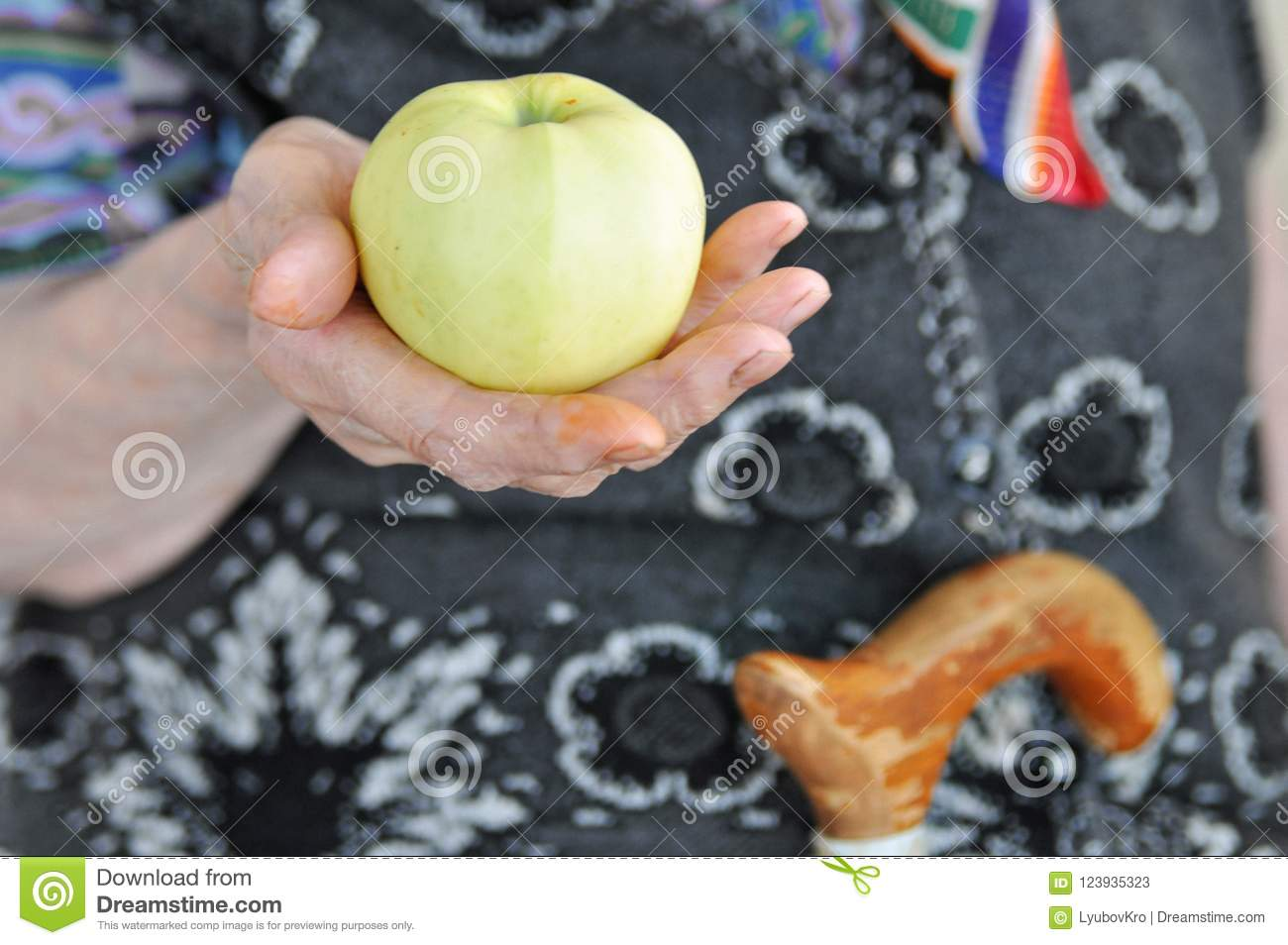 Ripe Apple in the hand of an elderly woman in a knitted vest for a walk. 90 years. Health and nutrition. Close-up