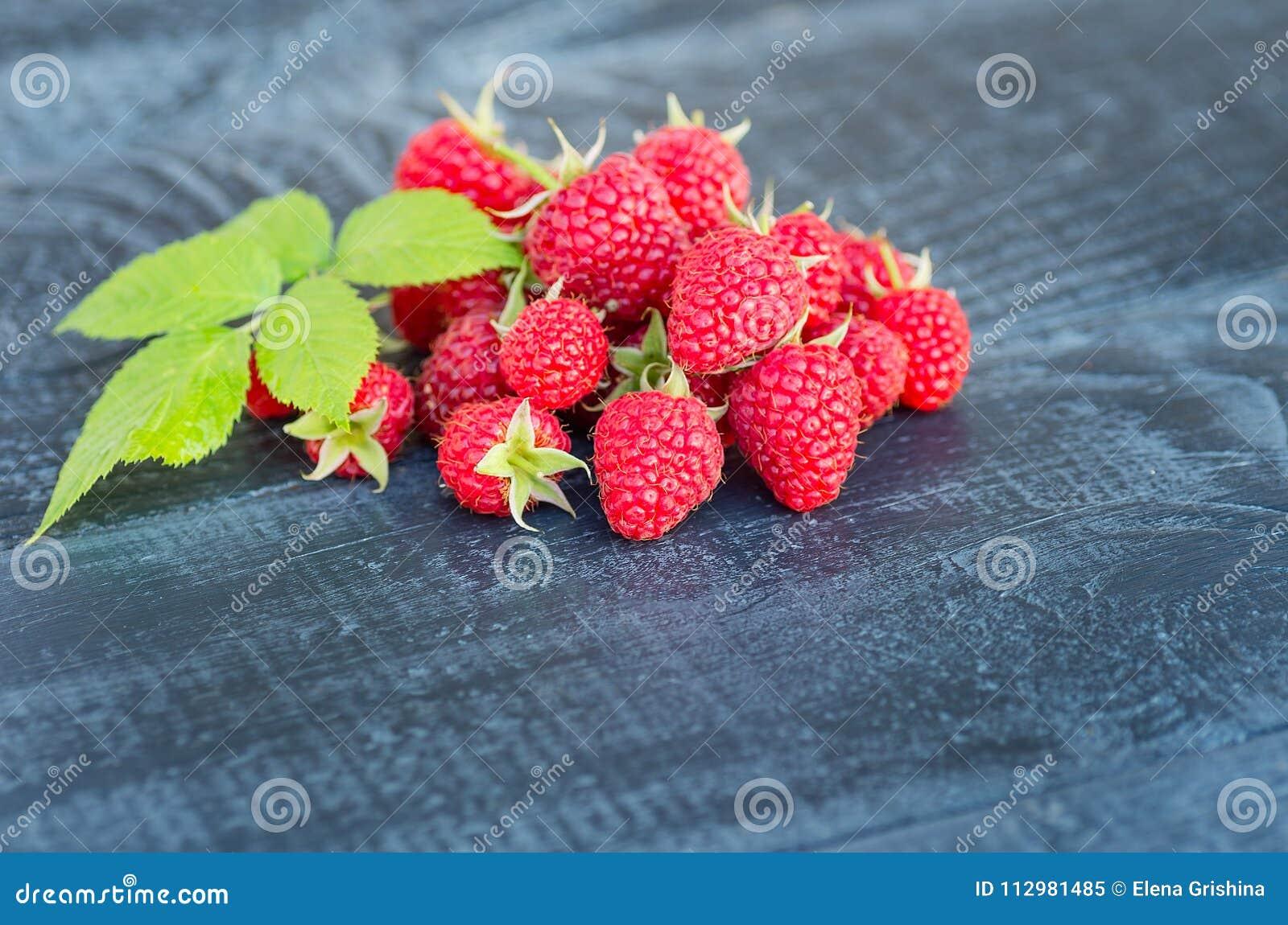 Ripe berries of raspberry garden. Rustic background.