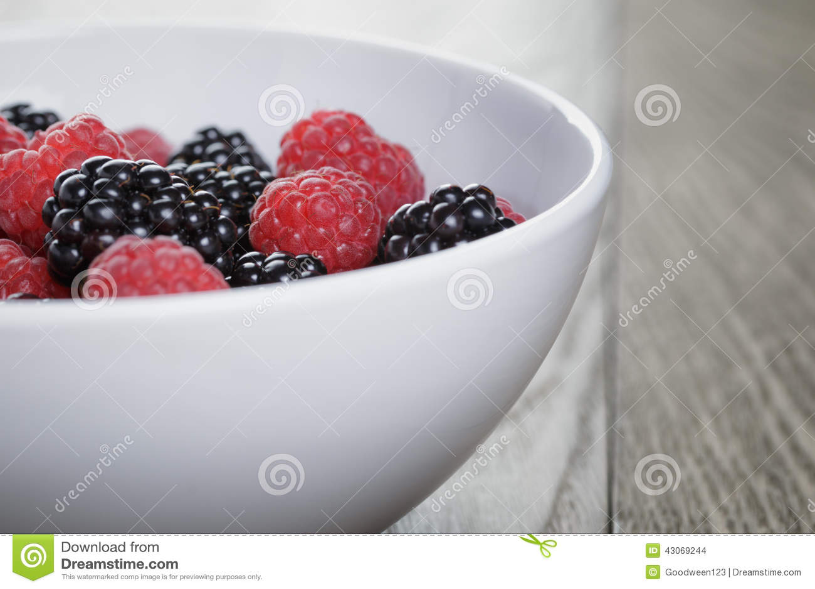 Ripe blackberries and raspberries in white bowl on old oak table