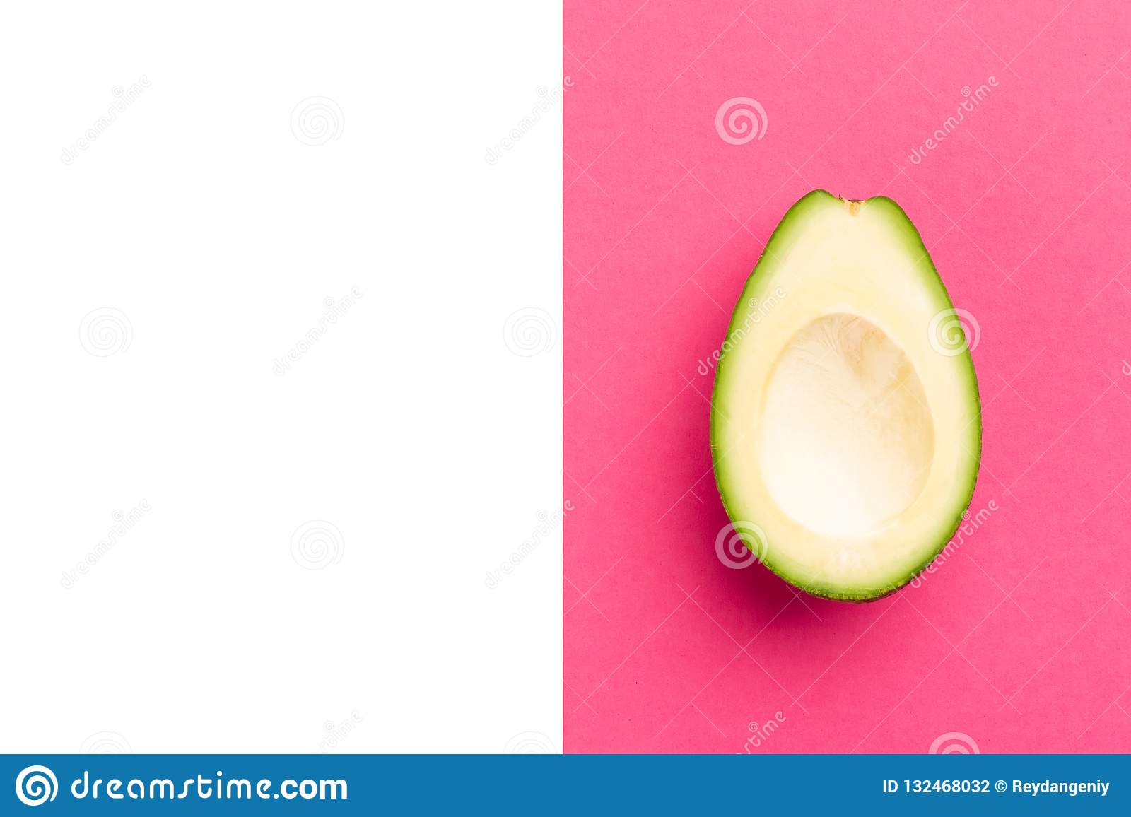 Ripe fresh cut pitted avocado fruit close-up on a pink