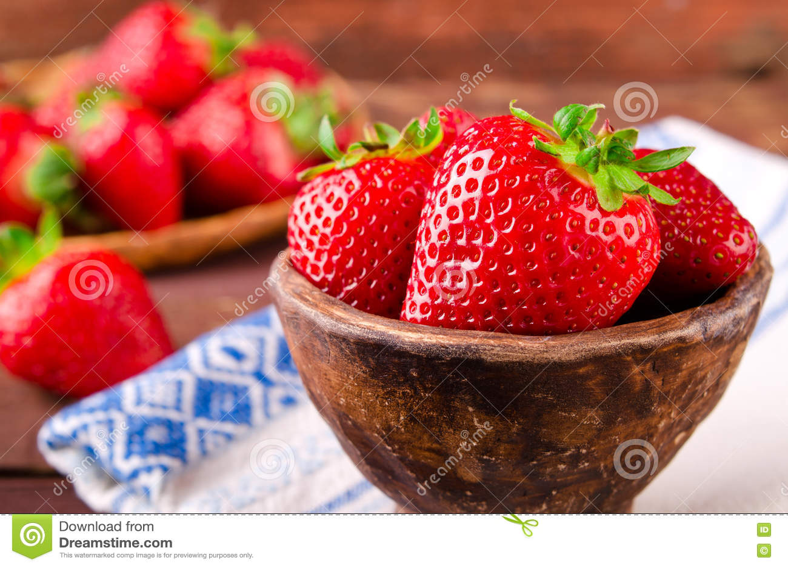 Ripe fresh juicy organic strawberries in old clay bowl