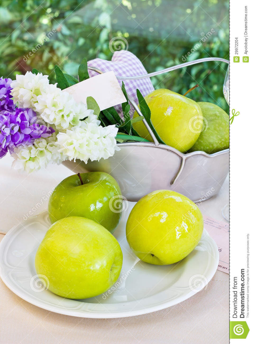 Ripe green apples and a vase with hyacinths on a p