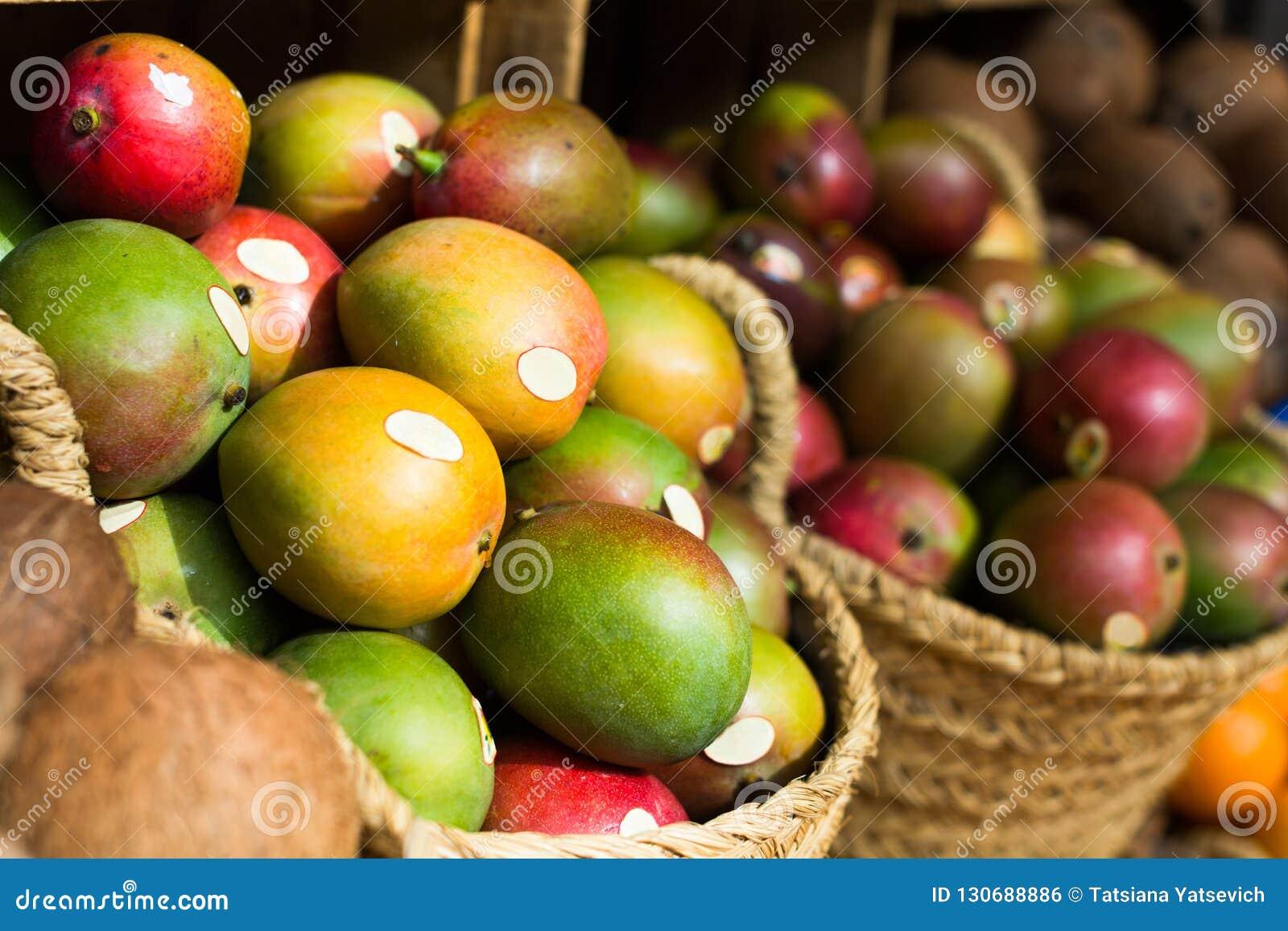 Ripe juicy mango in wicker baskets on market counter