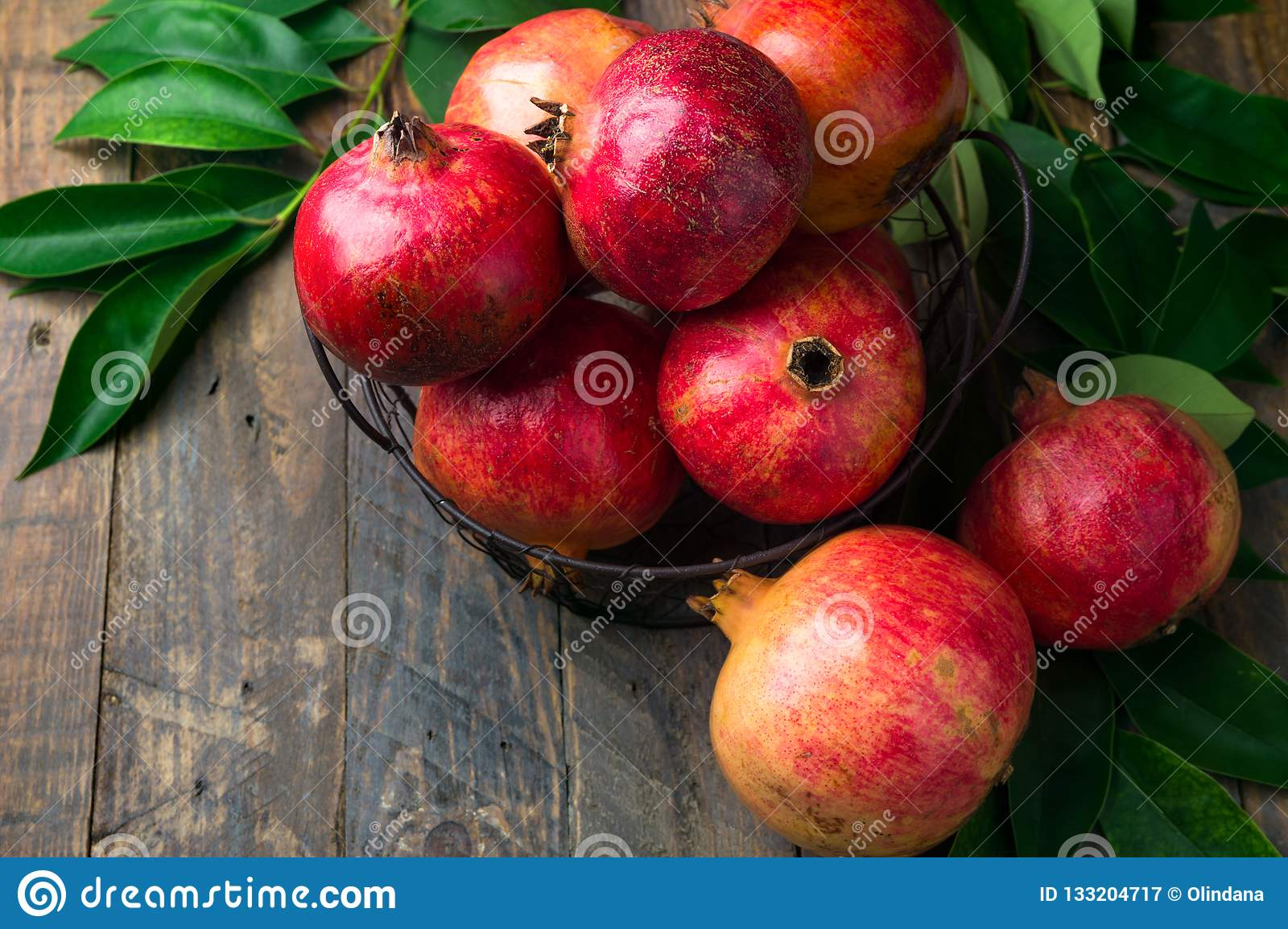 Ripe juicy organic bright red pomegranates in metal wicker basket with branches green leaves on plank barn wood background