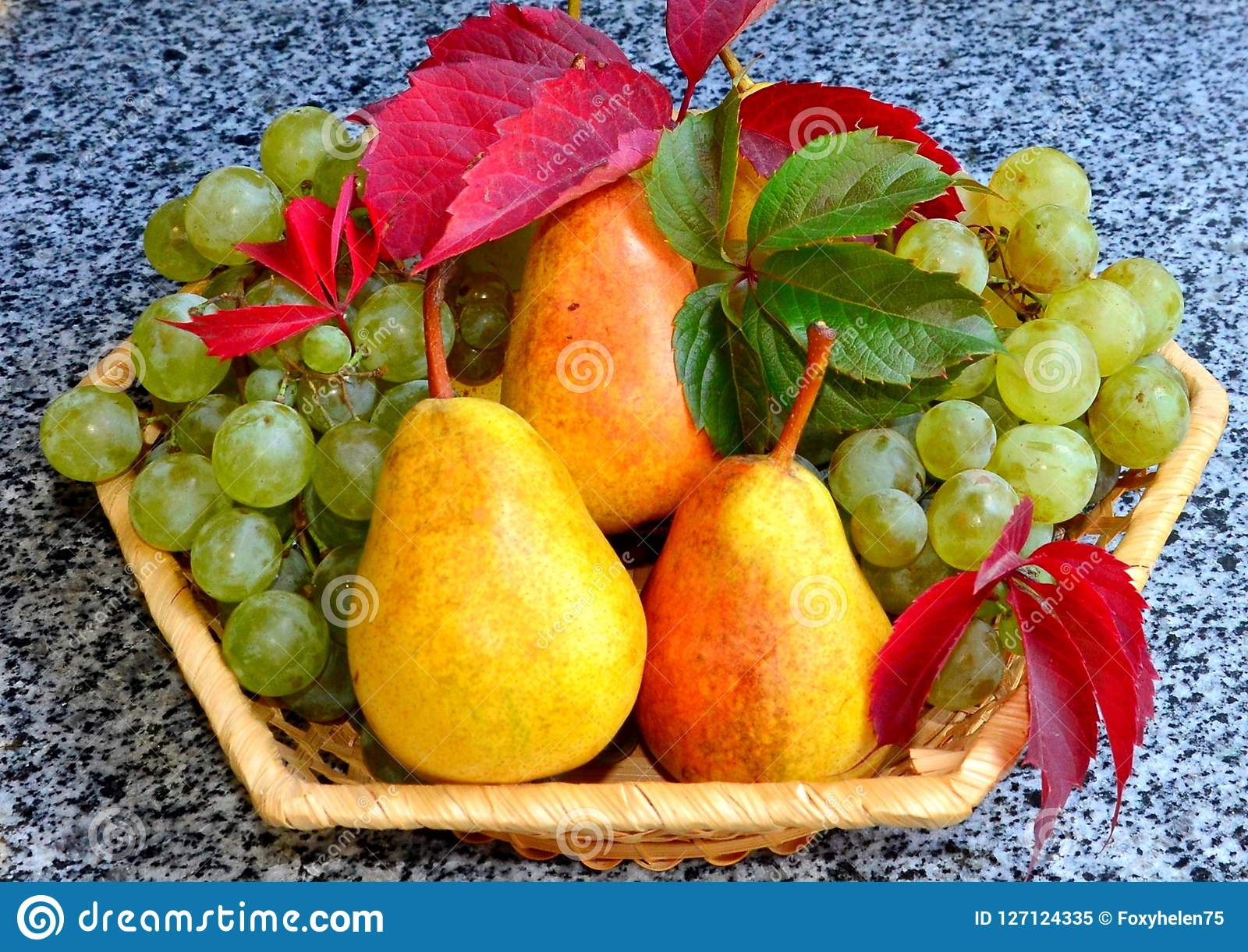 A ripe juicy pear lies on a table, in the background a vase with grapes and pears