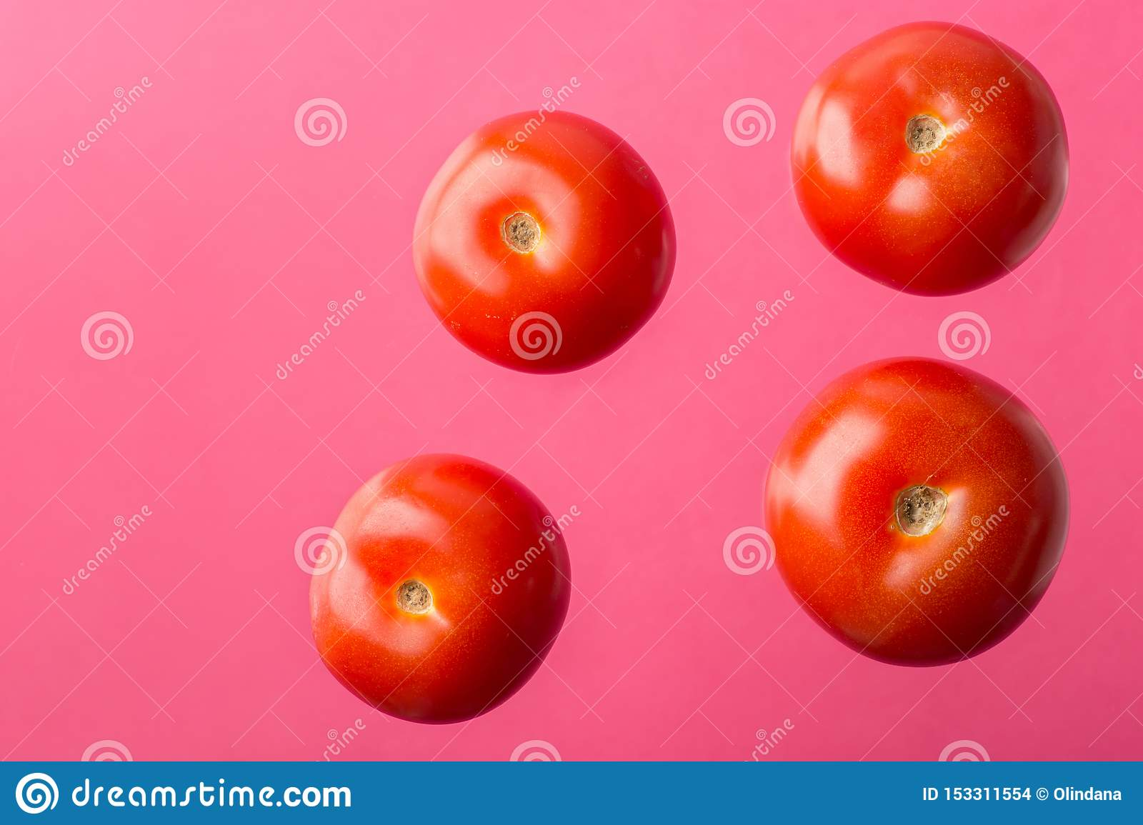 Ripe juicy tomatoes floating levitating in air on pink background. Creative food poster for Mediterranean cuisine healthy diet