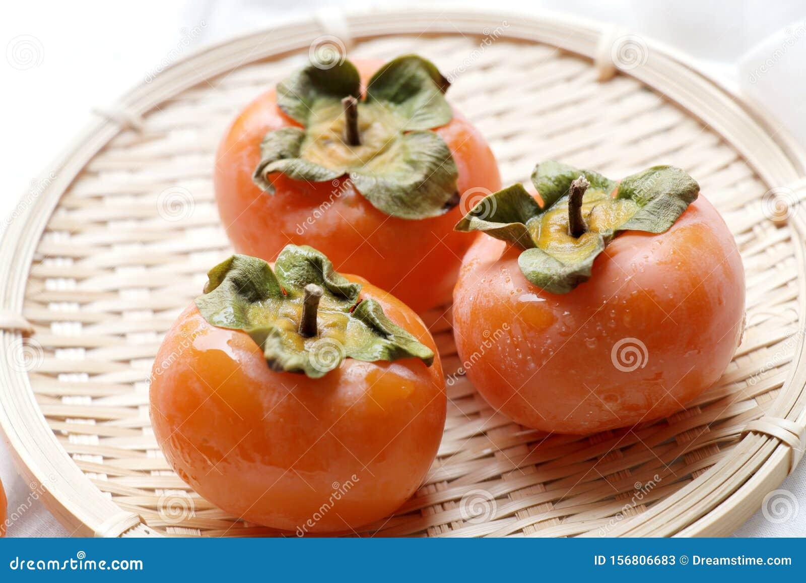 Fresh kaki on basket.Ripe orange persimmon fruit.