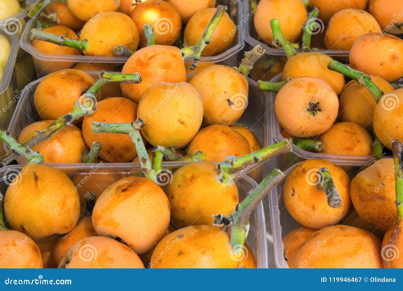Ripe Organic Vivid Orange Medlars in Boxes at Farmers Market in Spain. Bright Vibrant Vivid Colors. Vitamins Superfoods Harvest