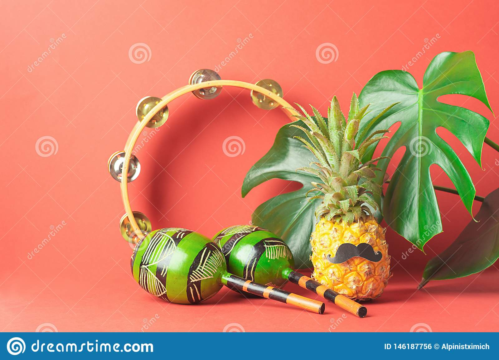 Ripe pineapple with a black mustache maracas tambourine large leaves of monstera on a red bright background.